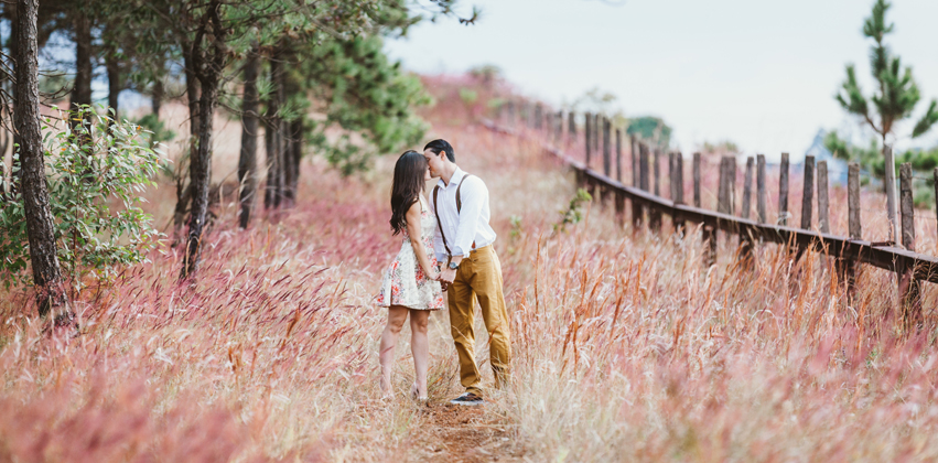 Man and woman holding hands and kissing in a beautiful field
