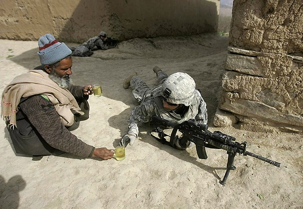 Humanity- Afghan man offering tea to American soldier